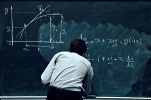 Teacher solving math problem on black board.
