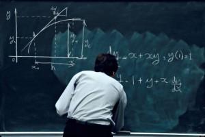 Teacher solving math problem on black board.